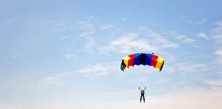 Red, yellow and blue parachute against cloudy sky