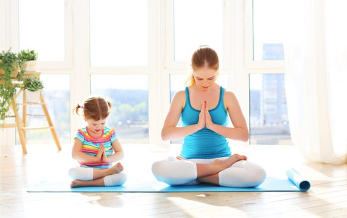 family mother and child daughter are engaged in meditation and yoga at home